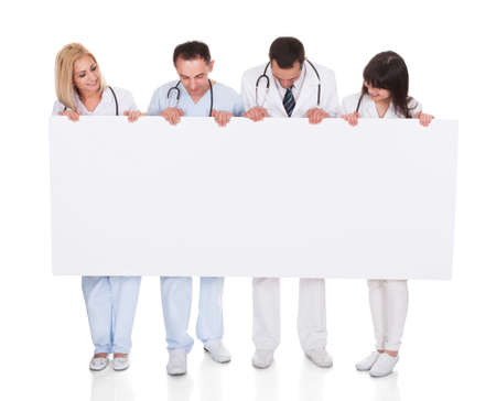Group Of Happy Doctors Holding Placard Over White Background photo