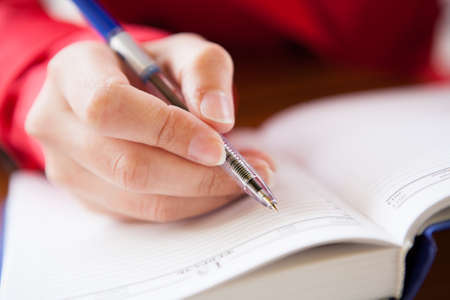 Close-up  of hand holding pen and writing in diary of hand writing in diary