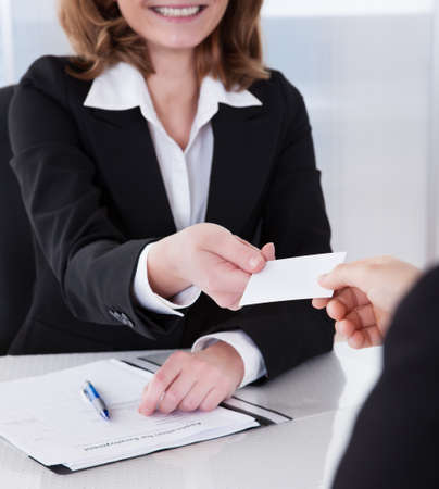 exchanging: Two happy businesspeople exchanging visiting card in office