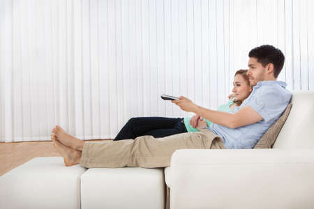 Young couple sitting on couch watching television photo