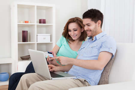 Portrait of young happy couple sitting on couch shopping online photo