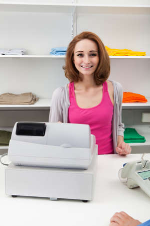 Gelukkig Jonge Vrouw kassier met Cash Register At Cash Counter