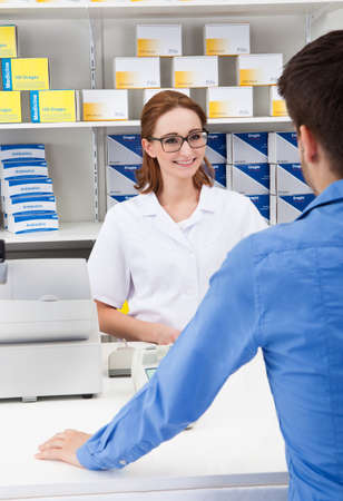 Happy Young Female Pharmacist In Pharmacy With A Client photo