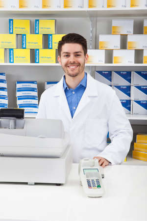 selling service smile: Portrait Of Happy Male Pharmacist In Pharmacy Stock Photo