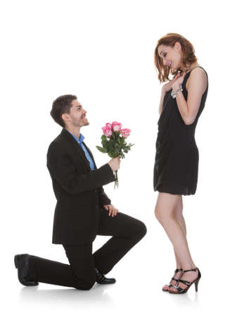 kneel: Young Man Offer Flower To Beautiful Woman Over White Background