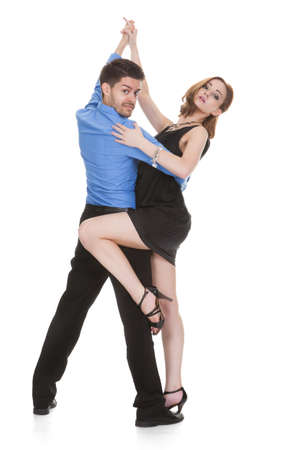 Elegant young couple dancing on white background photo