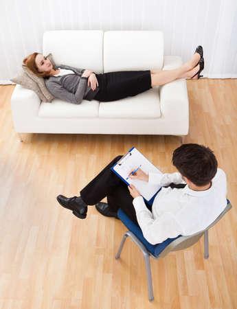 Business-Frau liegend auf einer Couch bequem im Gespr?ch mit seinem Psychiater etwas zu erkl?ren