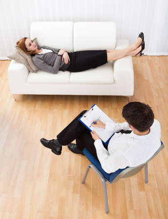 Business woman reclining comfortably on a couch talking to his psychiatrist explaining something