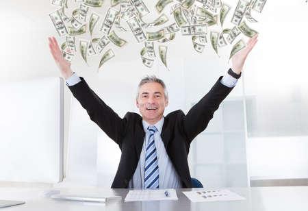 loteria: Feliz hombre de negocios maduro que levanta los brazos en el escritorio en la oficina Foto de archivo