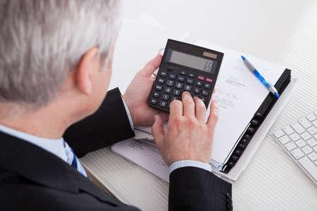 電卓: オフィスで財務計算する成熟した実業家の肖像画