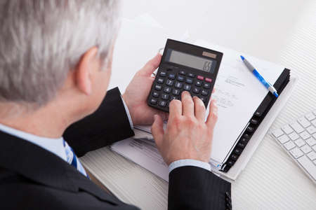 accountants: Portrait Of Mature Businessman Calculating Finance At Office