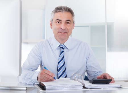 オフィスで財務計算する成熟した実業家の肖像画