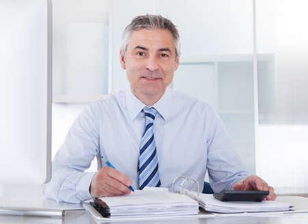 Retrato del empresario maduro cálculo financiero en la oficina