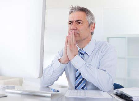 persona pensando: Retrato del pensamiento del hombre de negocios maduros en el escritorio en la oficina Foto de archivo