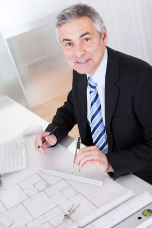 Portrait Of Mature Architect Male With Blueprint In The Office Stock Photo - 20504874