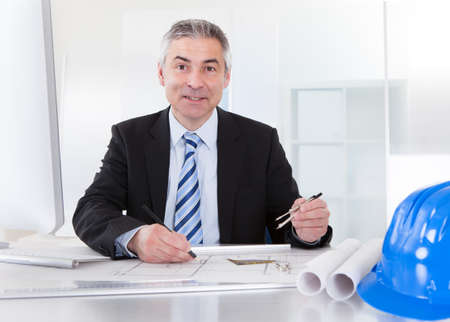 Portrait Of Mature Architect Male With Blueprint In The Office Stock Photo - 20504915