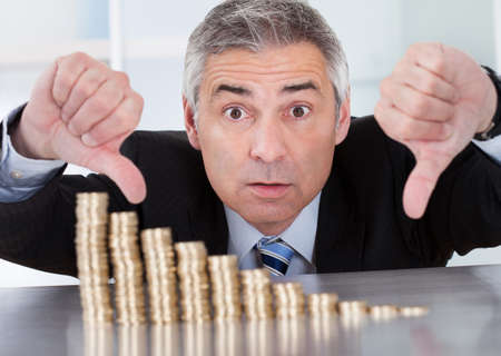 degrading: Shocked Mature Businessman Looking At Descending Stack Of Coins