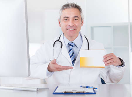Happy Mature Male Doctor Showing Medicine Box photo