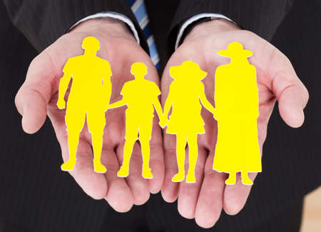 Close-up Of Male Hand Holding Family Cutout Shape Stock Photo - 20505082