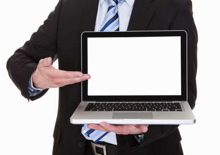 Happy Mature Businessman Pointing On Laptop Over White Background photo