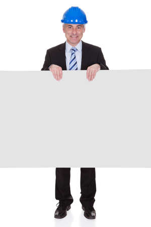 Mature Male Architect Holding Billboard Over White Background photo