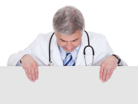 Portrait Of Male Doctor Holding Placard Over White Background Stock Photo - 20504814