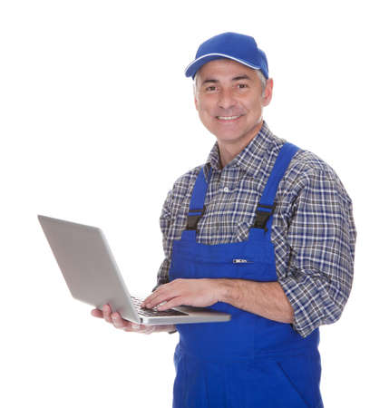 Érett férfi technikus segítségével laptop fölött fehér háttér