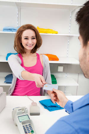 Client Handing Over Credit Card To A Happy Female Cashier Stock Photo - 20505074