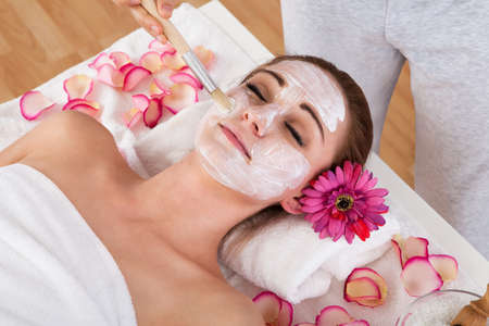 Beautiful young woman getting facial mask at spa studio photo