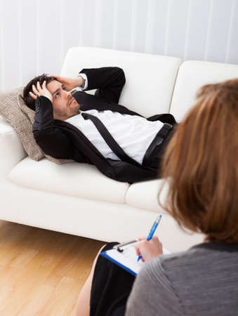 Business man reclining comfortably on a couch talking to his psychiatrist explaining something photo