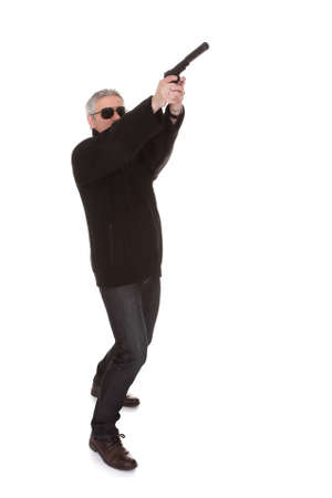 man holding gun: Mature Man Over White Background Aiming With Handgun