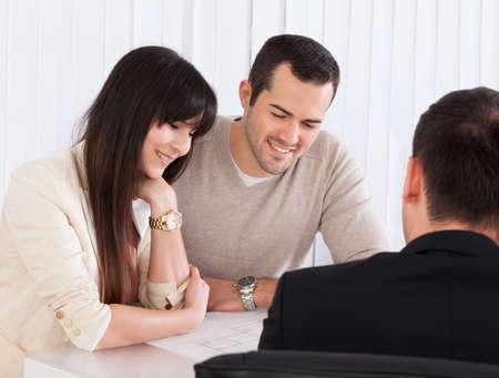 幸せな若いカップルのオフィスのコンサルタントとの議論