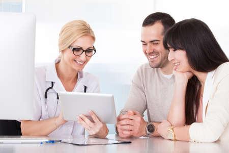 grupo de médicos: Doctor feliz que discuten con Couple In Clinic