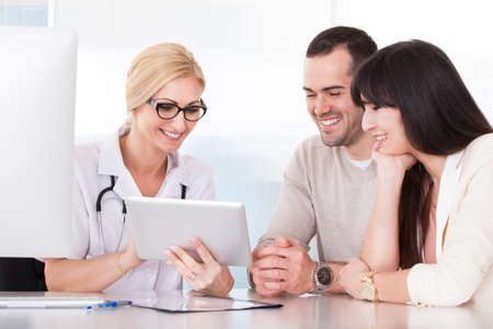 family doctor: Happy Doctor Discussing With Couple In Clinic