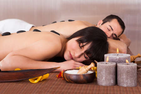 Beautiful Young Couple Enjoying Hot Stone Therapy In Spa Centre photo