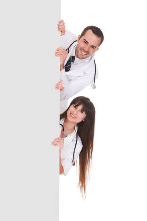 Two Happy Doctors With Placard Over White Background photo