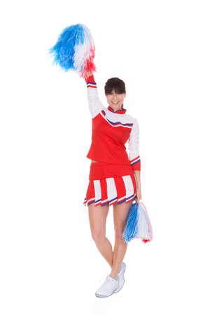 Happy Cheerleader Holding Pom-pom Over White Background photo