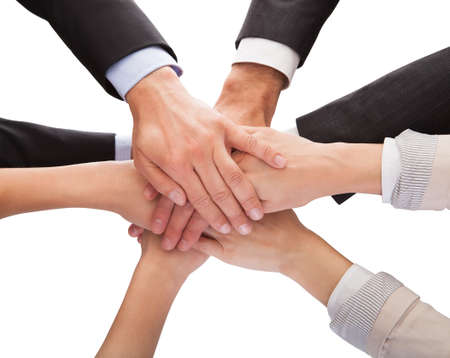 Close-up Of Businesspeople Hands Stacking Together Over White Background Stock Photo