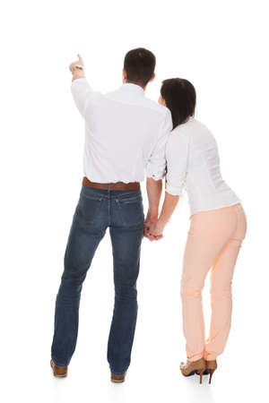 backside: Young Couple Holding Hands Over White Background