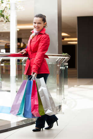 Happy young woman with shopping bags in mall photo
