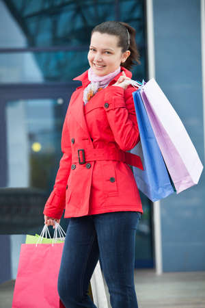 Happy young woman holding shopping bags; outdoors Stock Photo - 20535367