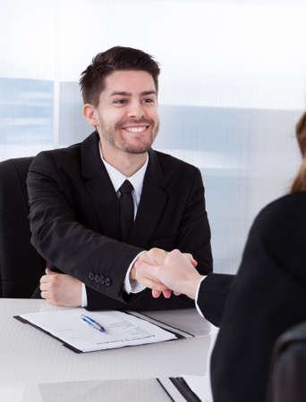 Two happy businesspeople in office shaking hands photo