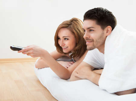 Young couple lying on mattress watching television photo