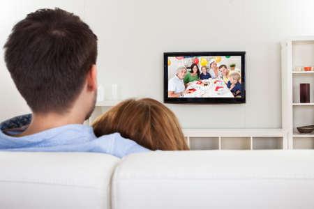 pareja viendo tv: Retrato de la joven pareja utilizando el port?til acostado en la cama