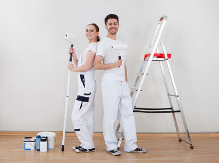 Portrait Of Young Happy Couple Holding Paint Roller Stock Photo - 20535363