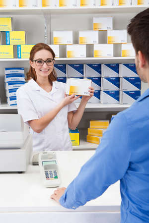 Happy Female Pharmacist Showing Drug In Pharmacy To Client photo