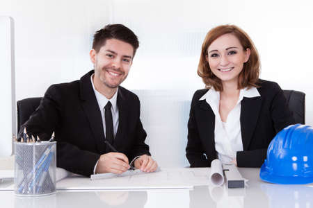 safety check: Portrait of two happy architects working in office