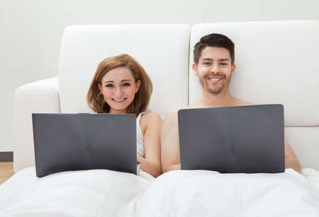 Portrait of young couple using laptop lying on bed photo