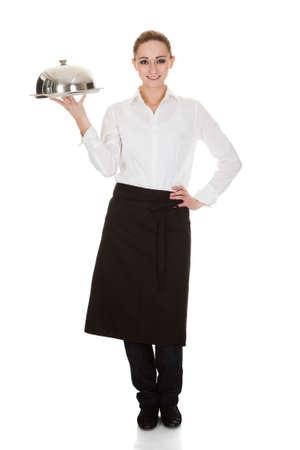 charolas: Feliz camarera joven que sostiene la bandeja y la tapa sobre el fondo blanco Foto de archivo