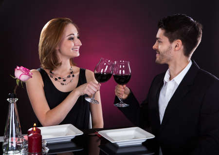 Happy young couple tossing wine in restaurant Stock Photo - 20535439